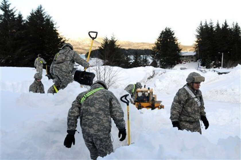 In this Jan. 8, 2012 photo provided by the Alaska National Guard, guard members help dig out the fishing town of Cordova, Alaska. Dozens of National Guard troops are helping Cordova recover from massive snows that have collapsed roofs, trapped some people in homes and triggered avalanches. (AP Photo/Alaska National Guard)