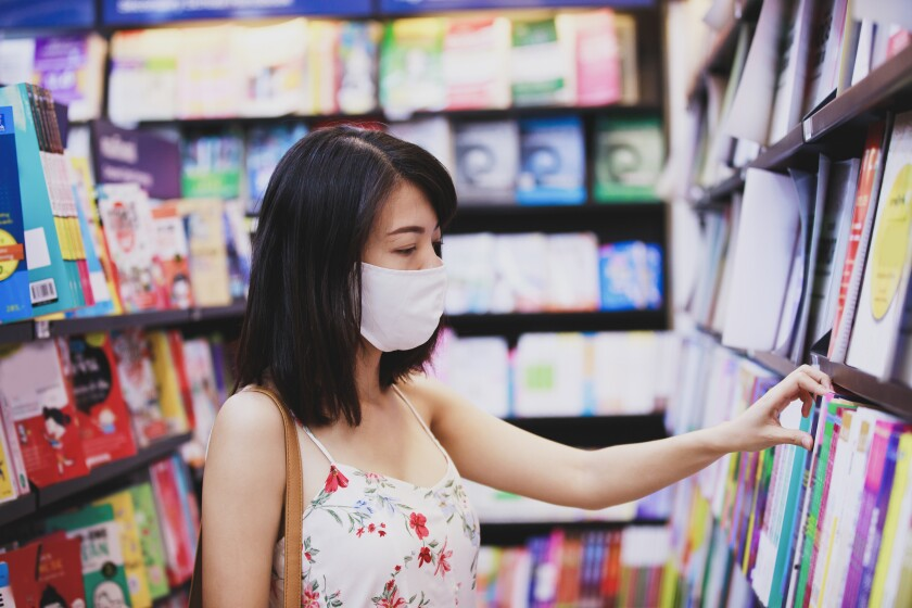 Asian woman wearing face mask choosing book magazine in book store.