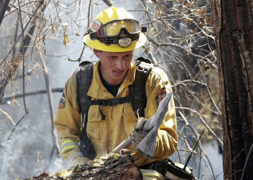 A Cal Fire firefighter works the front lines of a wildfire Sunday, Sept. 20, 2015, in Carmel Valley, Calif. The blaze burning north of the community of Jamesburg quickly grew after starting Saturday afternoon, the California Department of Forestry and Fire Protection said. (Vern Fisher/The Monterey County Herald via AP) MANDATORY CREDIT