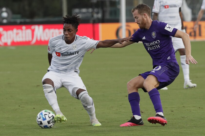 Orlando City midfielder Oriol Rosell, right, and Los Angeles FC forward Latif Blessing get tangled