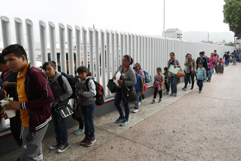 Men, women and children line up at a border fence.