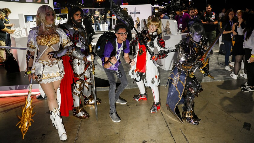 """At a past Con, Jeffrey Gates, center, who uses the Twitch handle thekelekter, posed with characters from the video game """"Lineage"""" in the exhibitors hall at TwitchCon."""