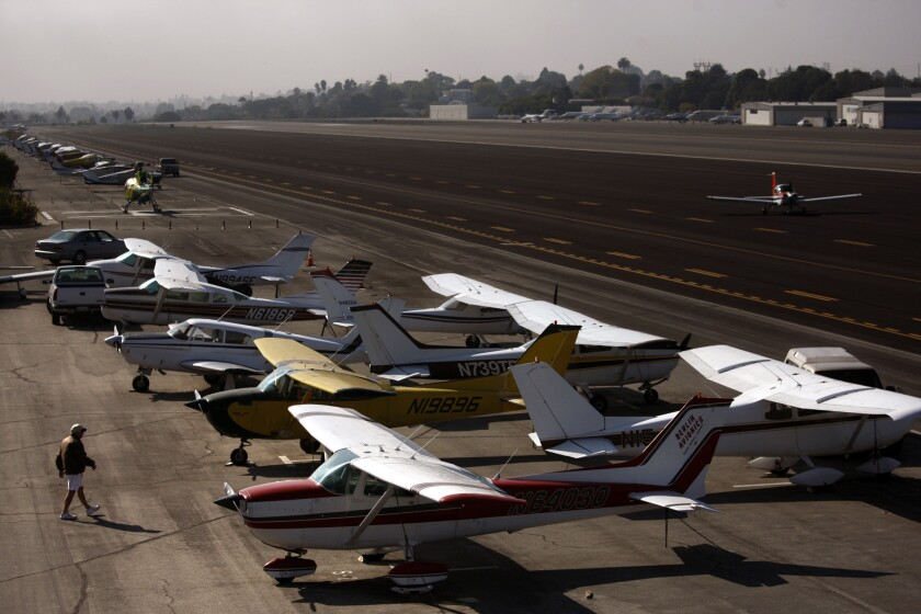 A man walks out onto the tarmac as a plane lands on the runway at the Santa Monica Airport. Community activists vowed to keep fighting to shut down the facility, despite a judge's dismissal of the city's lawsuit seeking ownership of the airport.
