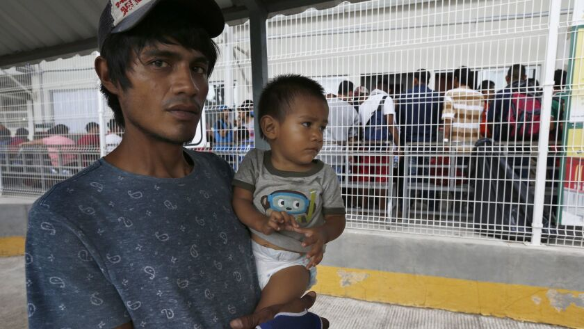 A man his son walk across the Suchiate river bridge as Central American migrants cross the border be