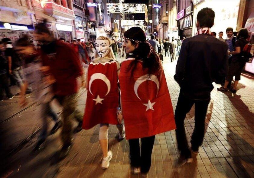 Jóvenes arropadas con banderas turcas caminan por la calle Istiklal, en la plaza de Taksim, en Estambul (Turquía), ayer. EFE