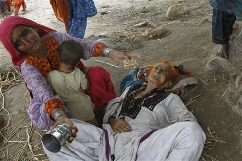 A Pakistani flood affected woman sits next to her mother Deenal Mai, 75, who was ill and exhausted due to hunger and thirst,  upon their arrival at Sukkur, in Pakistan's Sindh Province, Monday, Aug. 9, 2010.  The number of people suffering from the massive floods in Pakistan exceeds 13 million,  mo