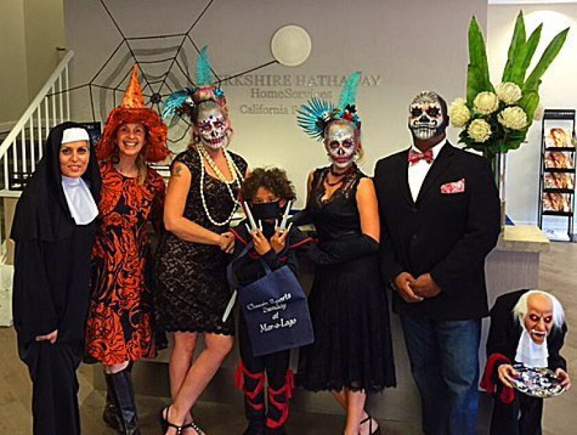 The La Jolla office of Berkshire Hathaway HomeServices California Properties was a spooky-safe place for kids to trick-or-treat on Halloween day during the annual Pillage the Village event sponsored by local Realtors, merchants and Kiwanis on Oct. Left to right are Candi DeMoura, Nick Marcellino, T