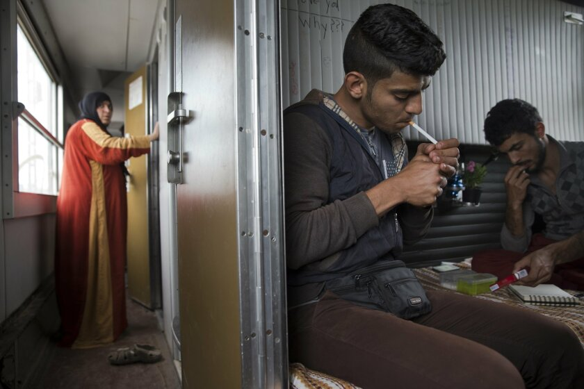 In this Sunday, May 8, 2016 photo, 23-year-old-Syrian man Mohamed lights a cigarette in his cousins cabin Majd Hamid , 22, as a Syrian woman Fatme gets in her  cabin inside a train car that they live in, in the sprawling refugee and migrant tent city if Idomeni, on Greece's northern border with Mac