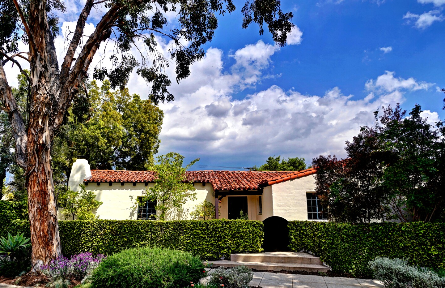 The Spanish Colonial Revival-style home, designed by George S. Hamrick, was built in 1925 buy local contractor Fritz Ruppel for his mother, Gertrude. The one-story residence, which has a clay tile roof and reinforced-concrete walls, was built at a cost of $7,000. Listed for $1.495 million, the charming residence opens to a grand living with cathedral-style ceilings, exposed beams and a wood-burning fireplace. The formal dining room sits off the kitchen, which has been updated with a stainless steel range and farmhouse-style sink. A French door in the kitchen leads outside to a small herb garden. The 1,825-square-foot floor plan has three bedrooms and two bathrooms. Tilework in one of the two bathrooms is reminiscent of the work of master craftsman Earnest Batchelder.