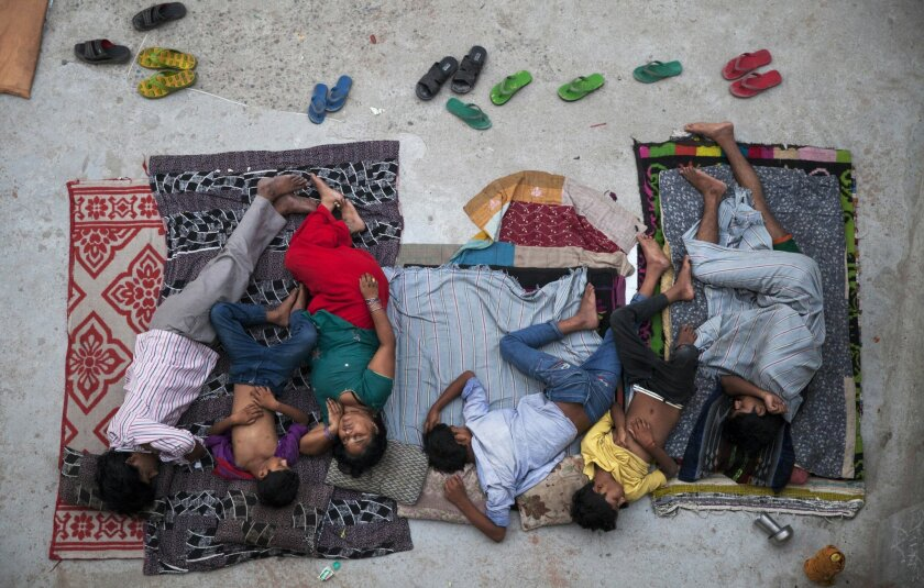 An Indian family sleeps on the roof of a house to beat the heat in New Delhi, India, Friday, May 29, 2015. In neighborhoods with irregular electric supply and sometimes to escape the heat that gets trapped in concrete houses in severely congested colonies people often sleep outside at night. (AP Photo/Tsering Topgyal)