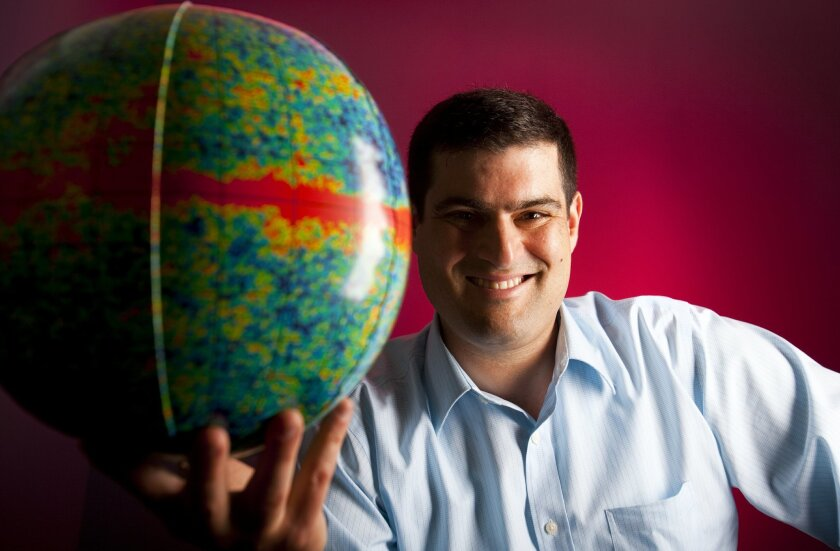 University California San Diego astrophysicist Brian Keating with a map of cosmic microwaves in the form of a blowup ball. Howard Lipin • U-T