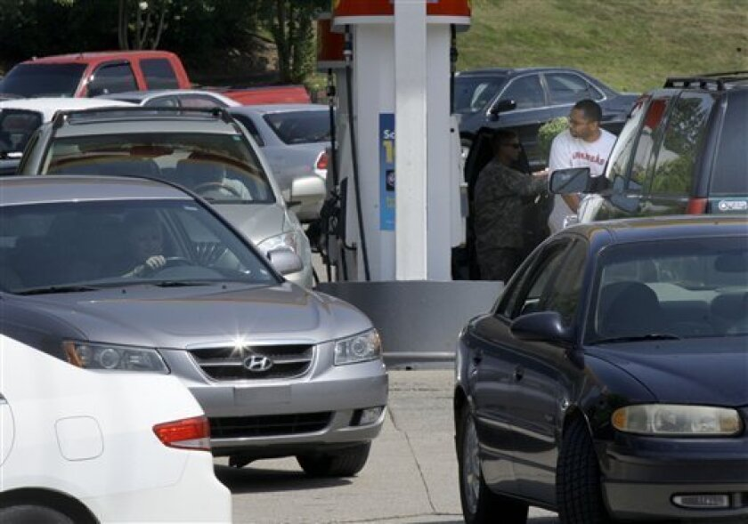 FILE - In this July 1, 2011 file photo, a man pumps gas at a crowded Shell gas station in Little Rock, Ark. Oil is climbing as analysts ratchet up price forecasts for next year as supplies get tighter.(AP Photo/Danny Johnston, file)