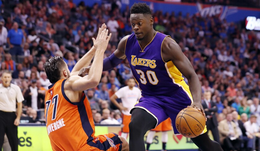 Lakers forward Julius Randle drives to the basket around Oklahoma City Thunder center Joffrey Lauvergne during the first half Sunday.