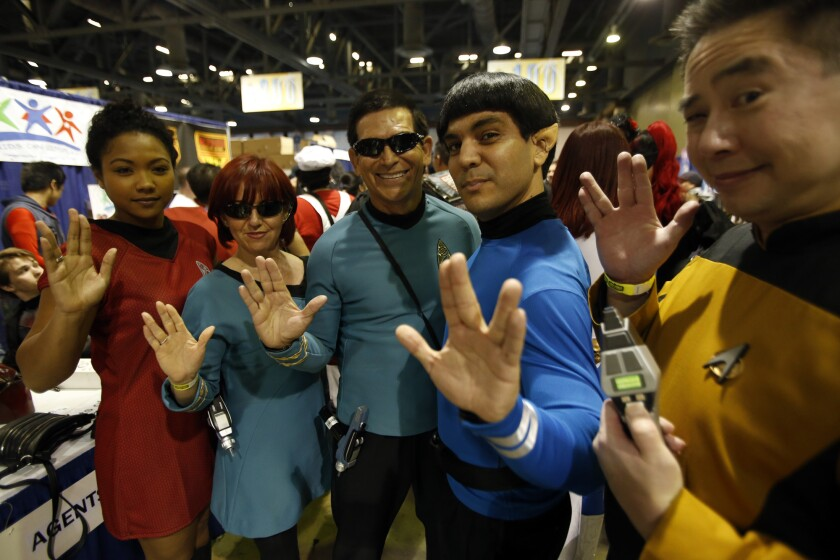 """Mamie Stiger, left, Idalia Mejia, Alfredo Garcia Jr., Richard Casillas and Sywa Sung give the Vulcan salute in memory of actor Leonard Nimoy at the Long Beach Comic Expo at the Long Beach Convention Center. """"I dressed like Spock,"""" said Casillas. """"It was something I had to do."""""""