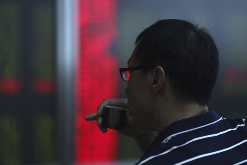 An investor drinks from a cap while monitoring stock prices at a brokerage in Beijing Wednesday, Sept. 25, 2019. Stocks skidded in Asia on Wednesday after Democrats in the U.S. House of Representatives said they were considered launching an impeachment probe of President Donald Trump. (AP Photo/Ng Han Guan)