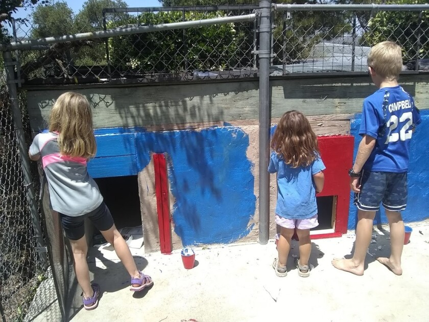 Claire, 6; Tessa, 3; and Davy, 8, painting the coop.