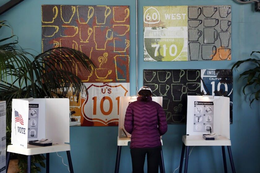 FILE - In this March 7, 2017 file photo, a woman votes at a polling station inside a coffee shop in Los Angeles. With the 2020 elections approaching, the latest California voter registration figures tell a familiar story: Democrats are expanding their ranks, Republicans are struggling and the fastest-growing group remains those voters aligned with no party at all - independents. The figures released Wednesday, Nov. 6, 2019 by Secretary of State Alex Padilla also show that more than 80 percent of eligible residents are registered to vote, the highest percentage since 1952. (AP Photo/Jae C. Hong, File)