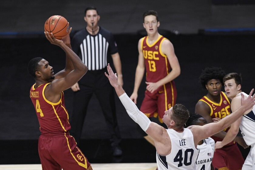Southern California's Evan Mobley, left, shoots over BYU's Kolby Lee in the first half.