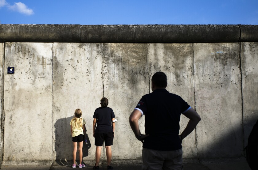 Visitors stand in front of remains of the Berlin Wall at the Wall memorial at Bernauer Strasse at the eve 60th anniversary of the construction of the Berlin Wall in Berlin, Germany, Thursday, Aug. 12, 2021. On Aug. 13, 1961 the East German government began constructing the Berlin Wall to split Berlin in an east and west part and marking a new step in the Could War between the western alliance and the communistic eastern block. (AP Photo/Markus Schreiber)