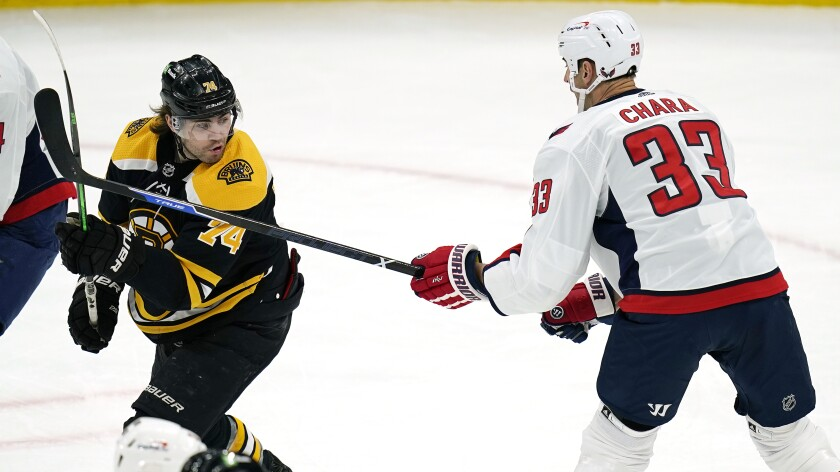Washington Capitals defenseman Zdeno Chara (33) pokes his stick at Boston Bruins left wing Jake DeBrusk (74) during the first period of an NHL hockey game, Wednesday, March 3, 2021, in Boston. (AP Photo/Charles Krupa)