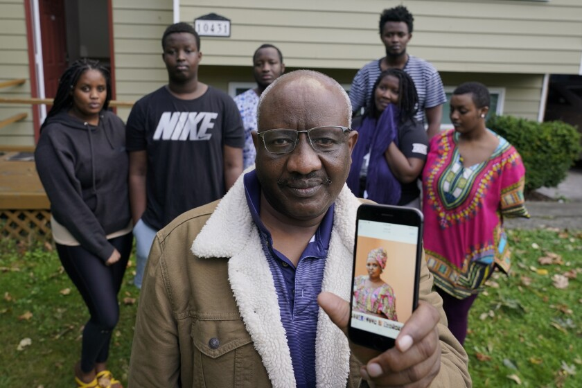 Sophonie Bizimana at his home in Kirkland, Wash., along with six of his children as he displays a photo of his wife.