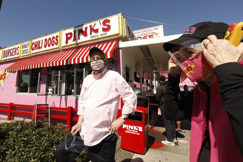Pink's Hot Dogs owners stand in front of the Melrose Avenue stand.