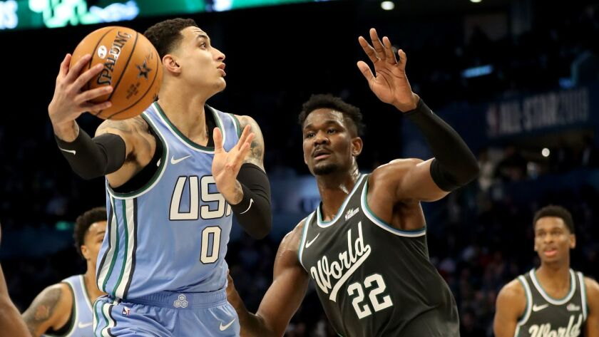 The U.S. team's Kyle Kuzma of the Lakers makes a move against the World team's Deandre Ayton of the Phoenix Suns during the Rising Stars game on Friday in Charlotte, N.C.