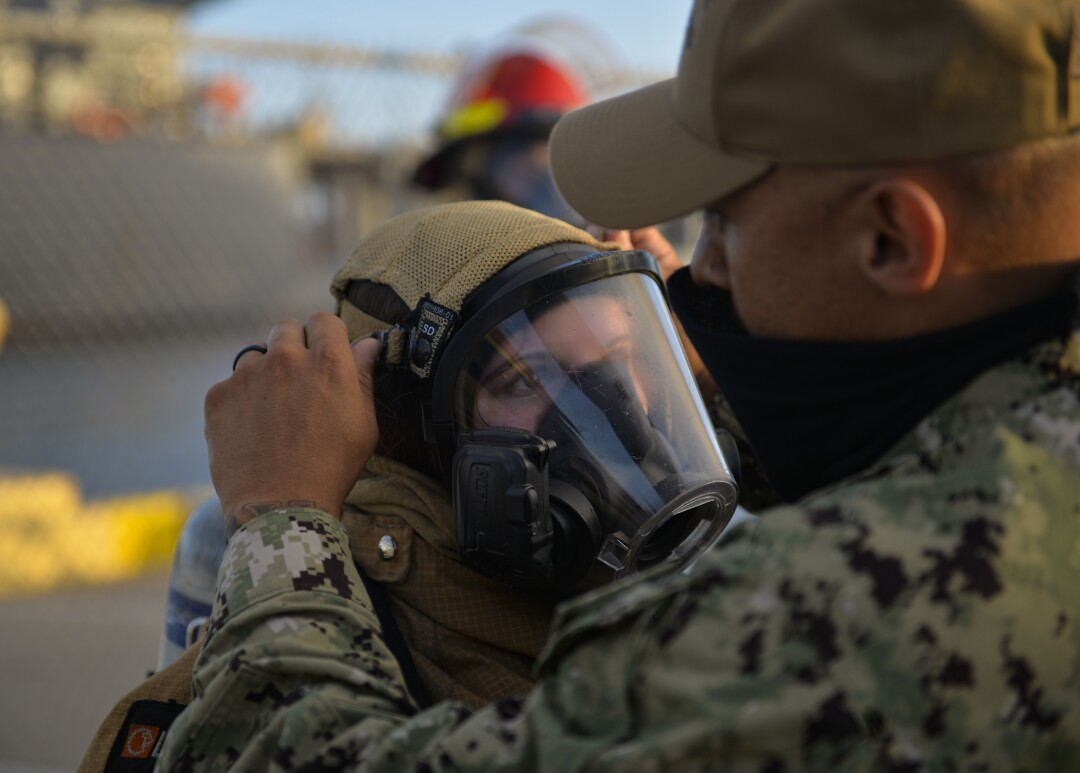 A U.S. Navy sailor is assisted in putting on her firefighting ensemble
