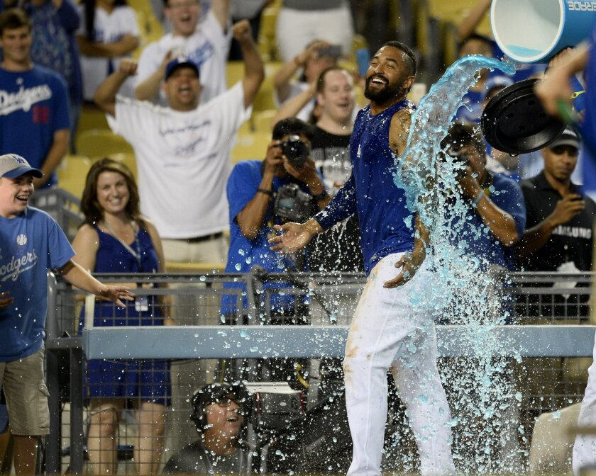 Dodgers outfielder Matt Kemp is doused with sports drink after his game-winning single in the bottom of the 10th inning against Atlanta on Wednesday night.