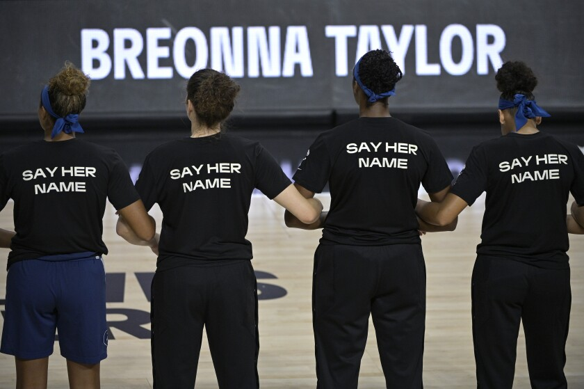 Minnesota Lynx players lock arms during a moment of silence in honor of Breonna Taylor