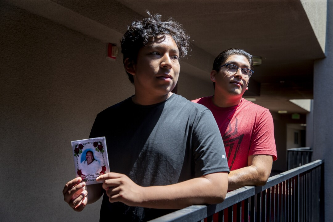 Two brothers pose for a portrait on an outdoor balcony, holding a photo of their late grandmother