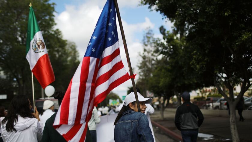 U.S. and Mexican flags are carried at a peace march near the border in Tijuana