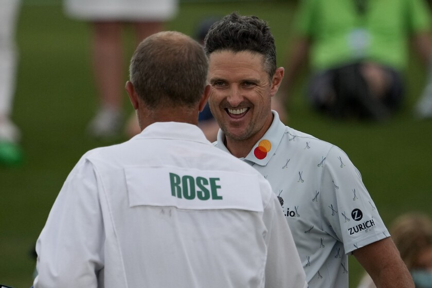 Justin Rose is all smiles as he's congratulated by his caddie David Clark after first round of the Masters.