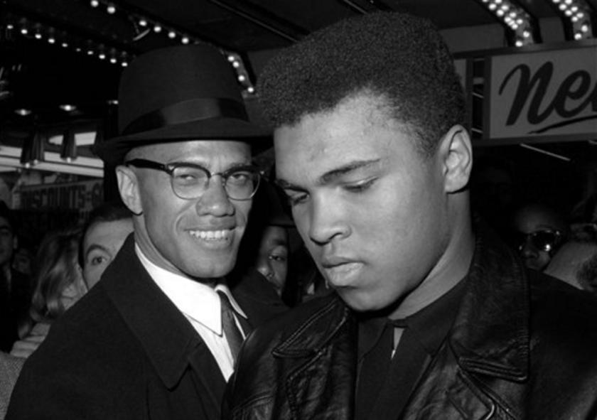 En esta foto de archivo del 1 de marzo de 1964, el campeón mundial del peso completo, Muhammad Ali, derecha, y el líder musulmán Malcolm X, aparecen a las afueras de un cine en Nueva York. Ali falleció el viernes, 3 de junio de 2016, a los 74 años. (AP Photo)