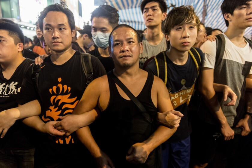 Protesters with the Hong Kong democracy movement form a chain in the Kowloon district on Oct. 3.