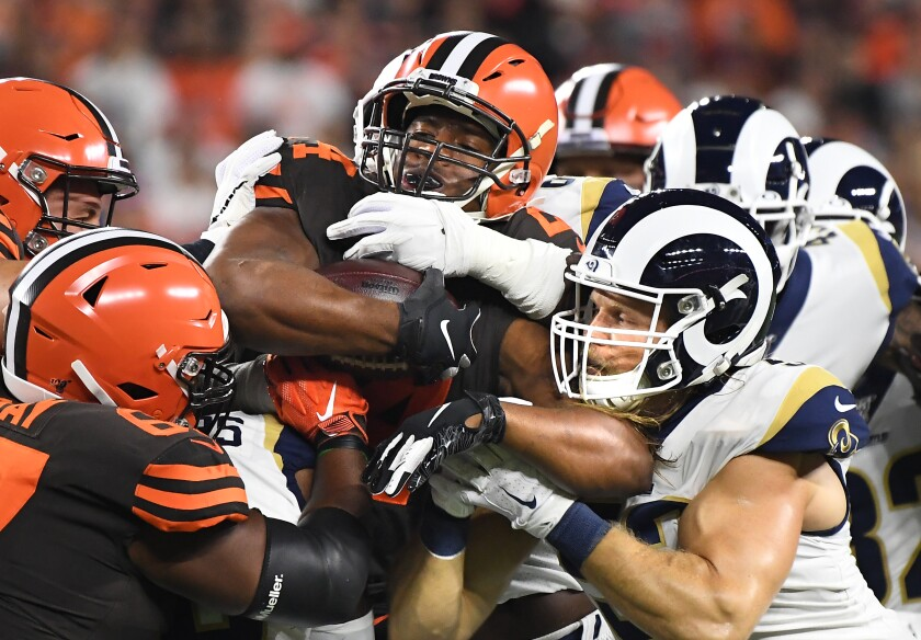 Clay Matthews, right, helps the Rams defense stop Browns running back Nick Chubb on Sunday night in Cleveland.