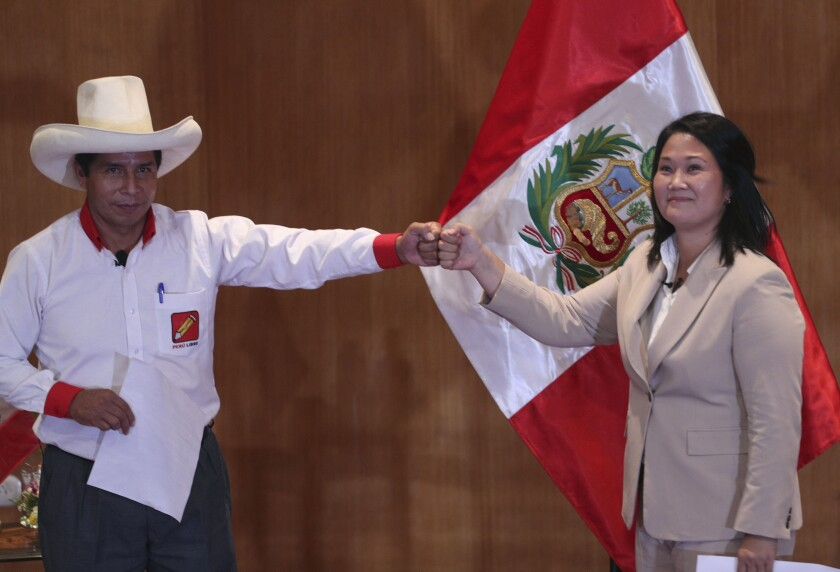"""Free Peru party presidential candidate Pedro Castillo, left, bumps fists with rival candidate Keiko Fujimori, of the Popular Force party, at the Peru Medical School in Lima, Peru, Monday, May 17, 2021. The candidates took an oath coined the """"Citizens Proclamation"""" that commits the winner of the June presidential election to defend democracy, to fight COVID-19, to defend the right to life, to guarantee human rights and freedom of the press, as well as to leave the presidency after five years and not seek reelection. (AP Photo/Martin Mejia)"""