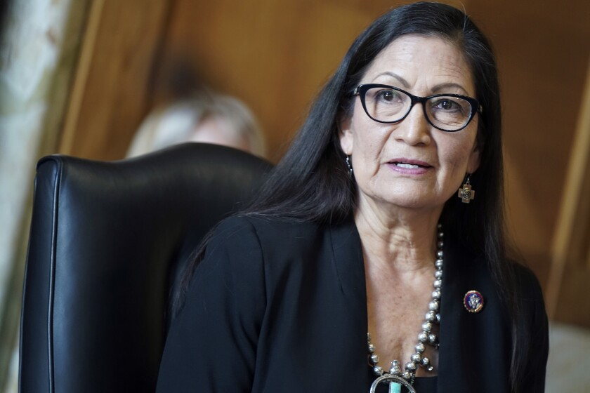 Deb Haaland speaks while seated in a black chair