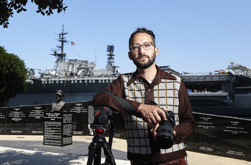 Filmmaker Evan Apodaca, holding a camera, is photographed near the Midway Museum.