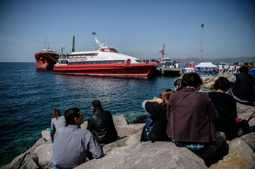 People gather on the beach as migrants deported from Greece arrive aboard a small Turkish ferry in the port of Dikili district in Izmir, Turkey, on April 4, 2016.
