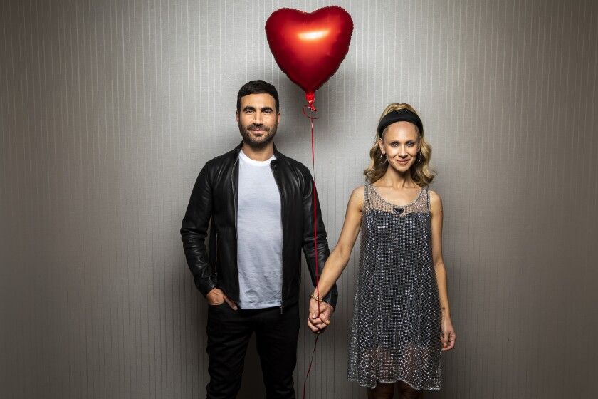 Actors Brett Goldstein and Juno Temple holds hands and a red balloon