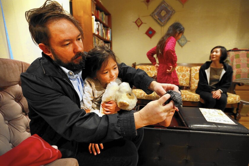 Nate Heneghan, helping his 4-year-old daughter Ada with her socks, is one of about 430 non-tenure-track faculty members at USC awaiting results of a vote on whether to be represented by SEIU Local 721.