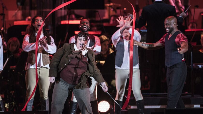 Rebel Wilson, left, who plays LeFou, waves a ribbon with Tye Diggs, right, who plays Gaston, during