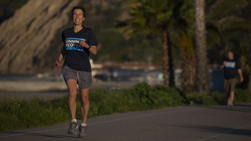 SANTA MONICA, CALIF. - MARCH 16: Leslie Gold, the coach of the Running for Recovery Group runs along