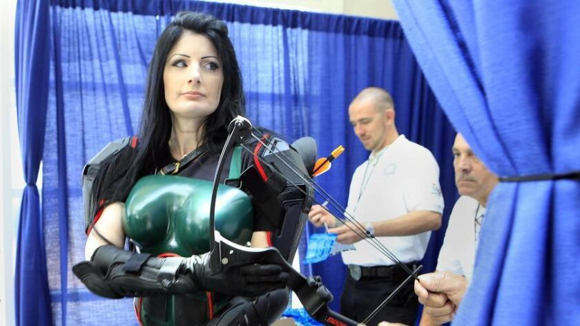 Denise Hanson of Riverside, CA had her bow and arrows checked at the security desk at Comic-Con. She is dressed as Robin Hood from the Heroes of Echo Company.