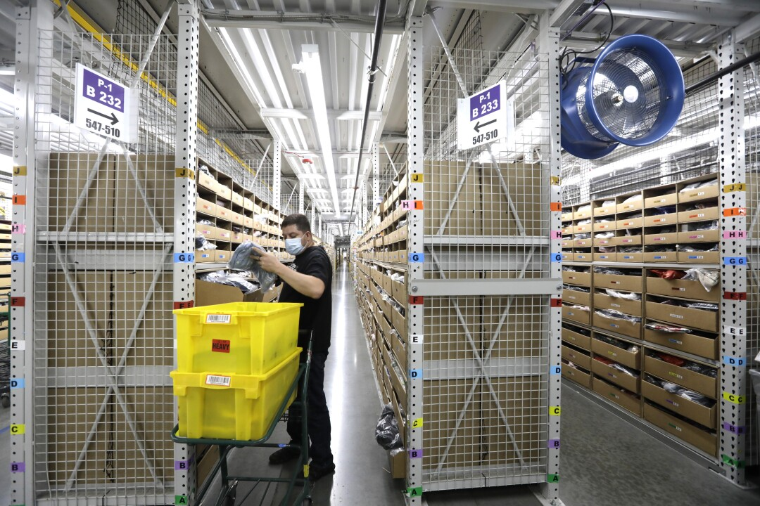 A warehouse worker handles merchandise next to two yellow bins