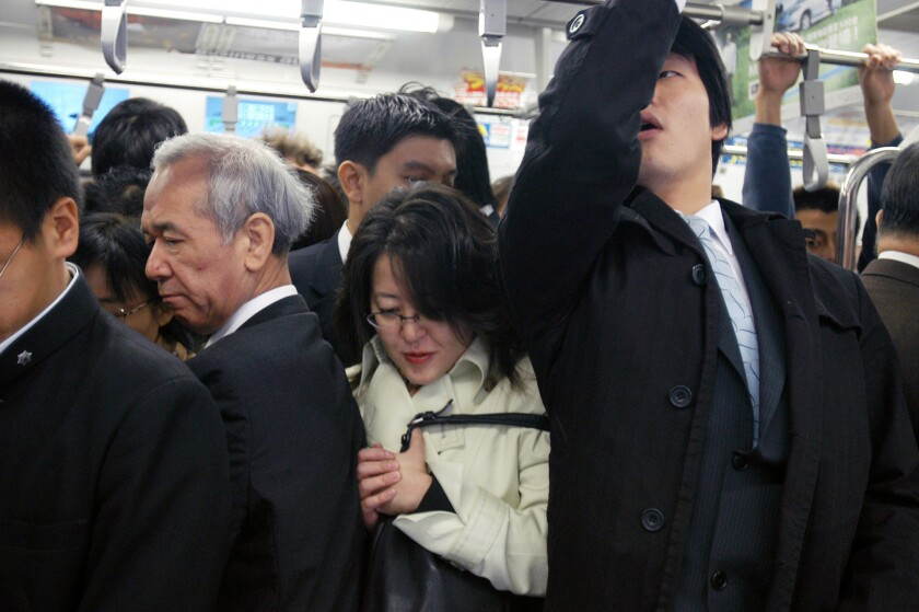 A Japanese woman squeezes in among Japanese businessmen aboard a crowded subway train during the morning rush hour in Tokyo. A university study says having airplane passengers stand during short flights can lower the fare by up to 44%.
