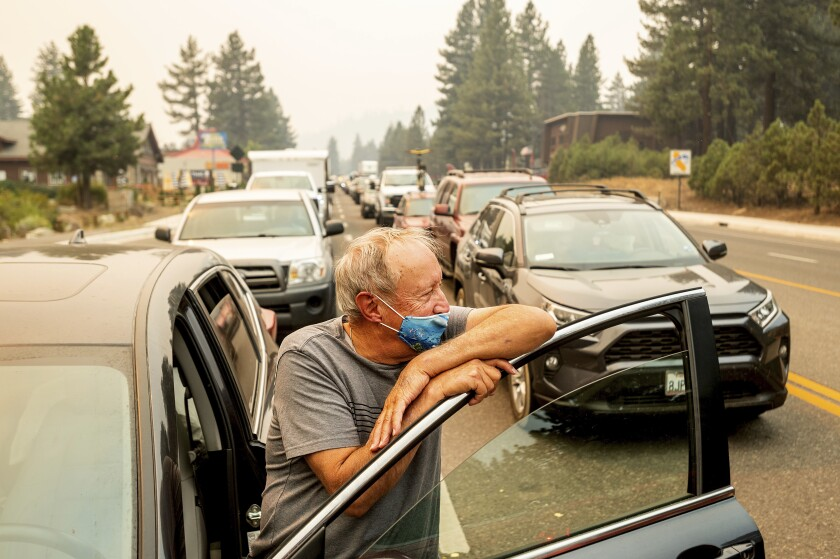 A man leans on his car door amid gridlocked traffic.