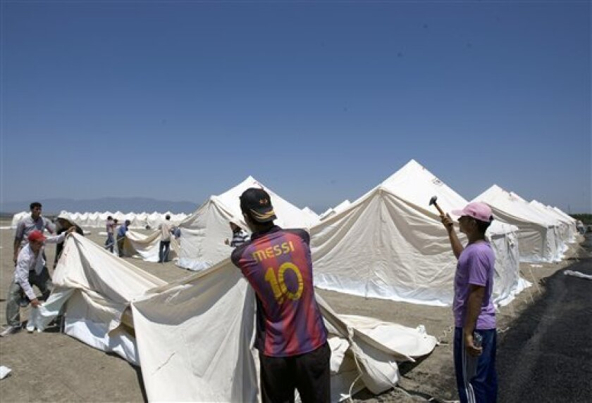 Turkish Red Cresdent workers pitch tents in a new camp that can receive up to 15,000 people for possible Syrian refugees in the Turkish town of Apaydin in Hatay province, Turkey, Friday, June 24, 2011.(AP Photo/Burhan Ozbilici)