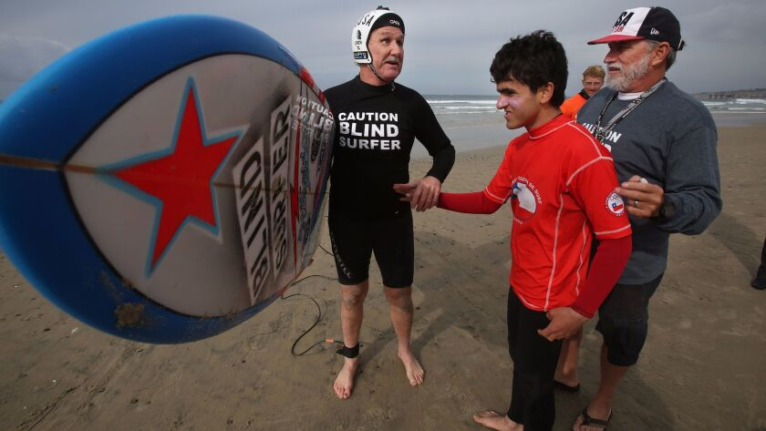 Scott Leason, left, greets fellow blind surfer Lucas Retamal, 16, from Chile, at La Jolla Shores on Wednesday. At right is Leason's coach Pat Weber. Leason and Retamal will compete in the 2016 Stance ISA World Adaptive Surfing Championship, that runs Dec. 9-11 at the Shores.